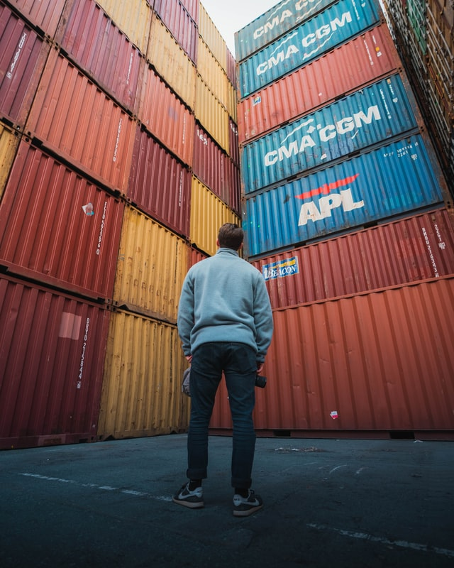 Man looks up at large stacks of shipping containers, he is almost surrounded by them.